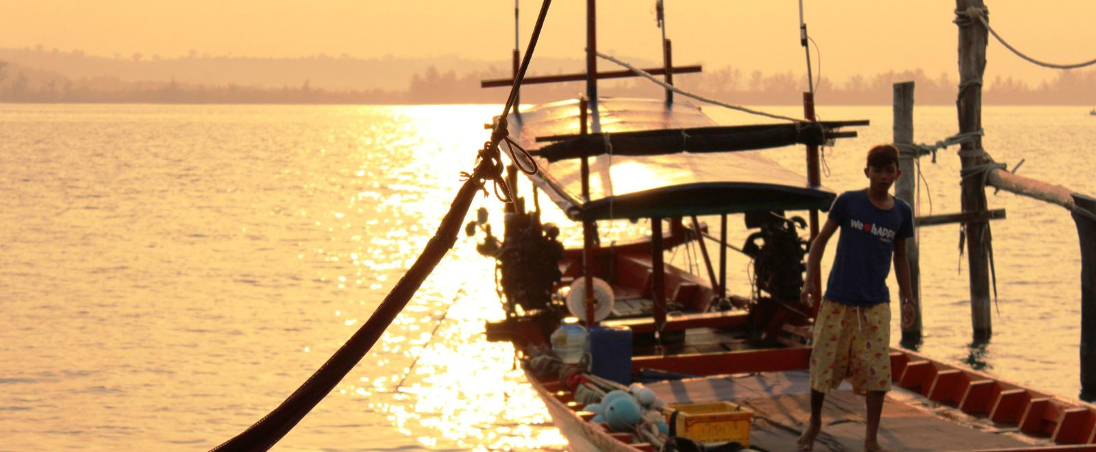 A local fisherman prepares a boat for a group of volunteers on a trip to experience Khmer cultural immersion.